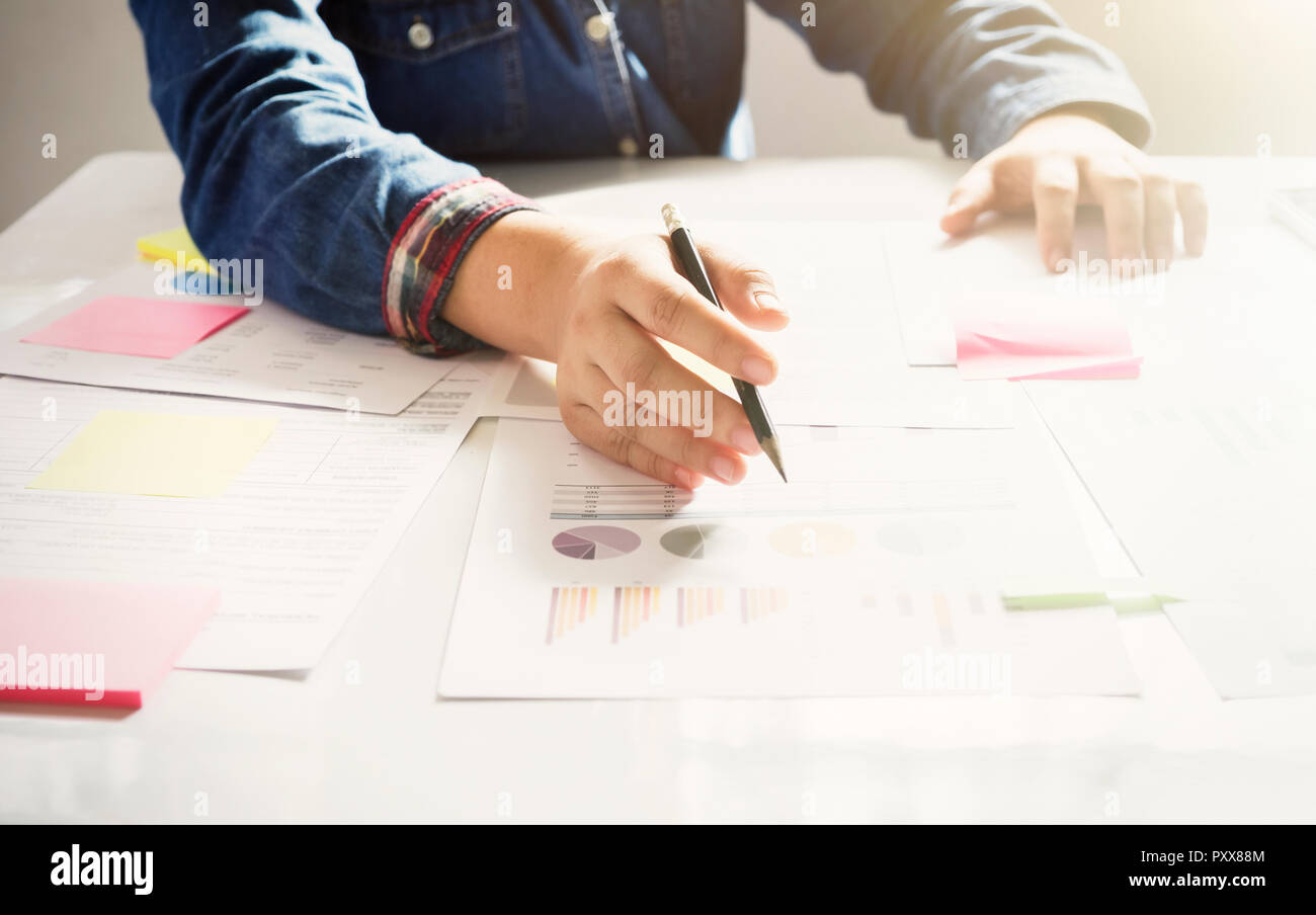 Startup business woman working with business documents on office table with  graph financial diagram. - Stock Image