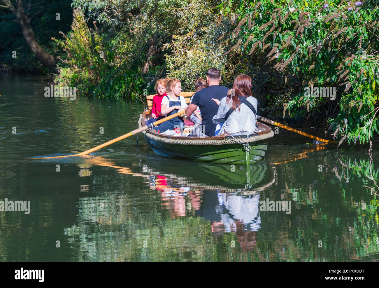 Family in a small rowing boat showing reflections in the water on a canal in Autumn, UK. - Stock Image