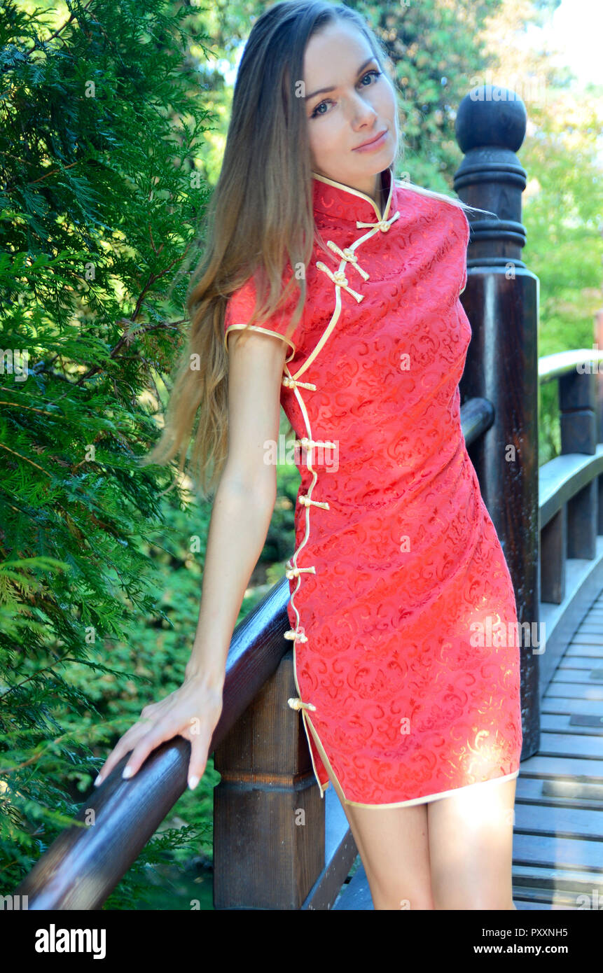 5724a4ba3 Female model from Poland wearing traditional Chinese dress in red color.  Woman stands on wooden