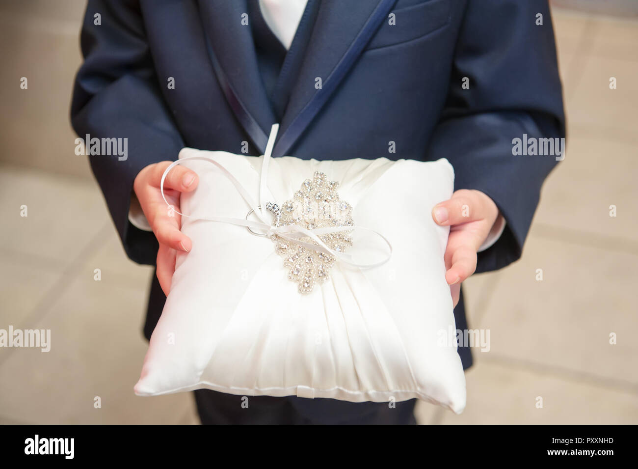 A young boy holds on to the pillow as part of his duties as ring bearer at a wedding. Stock Photo