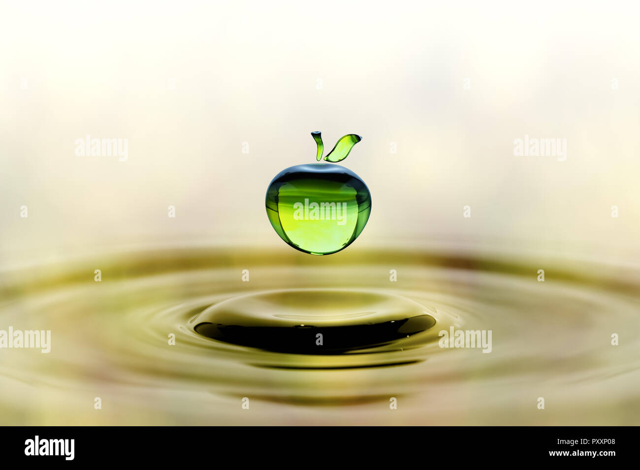 Rain drop in shape of green apple falling on blue water surface. Light brown blurred pattern in background. - Stock Image