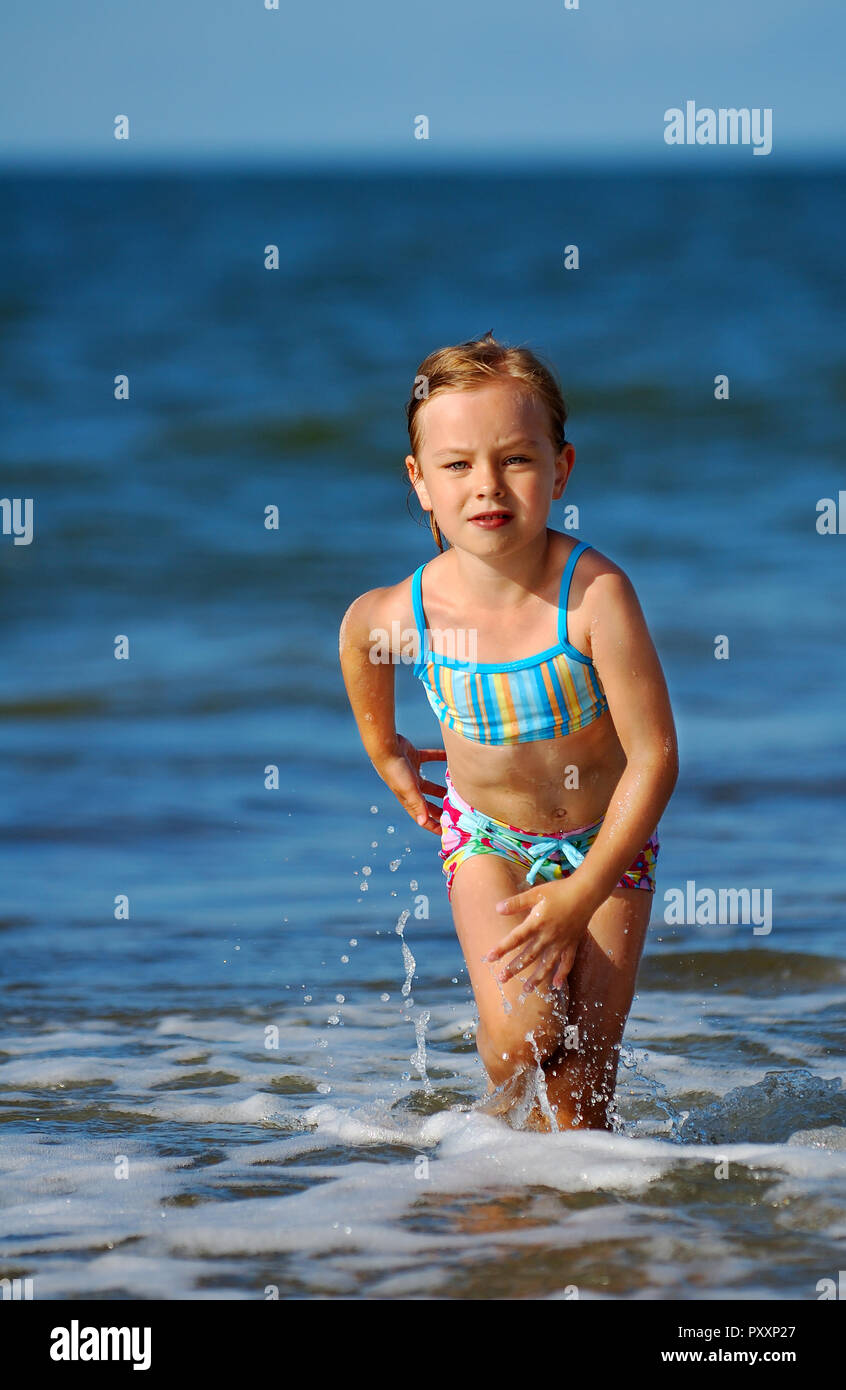 e143504241957 Cute little girl in swimsuit running on the beach, the blue sky in  background