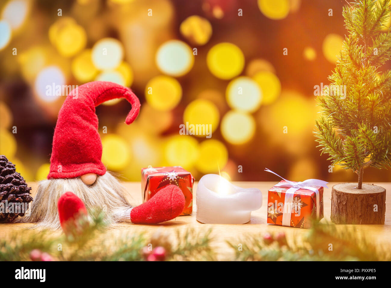Sitting christmas elf with bokeh lights in background surrounded by christmas decorations as tree and gift boxes - Stock Image