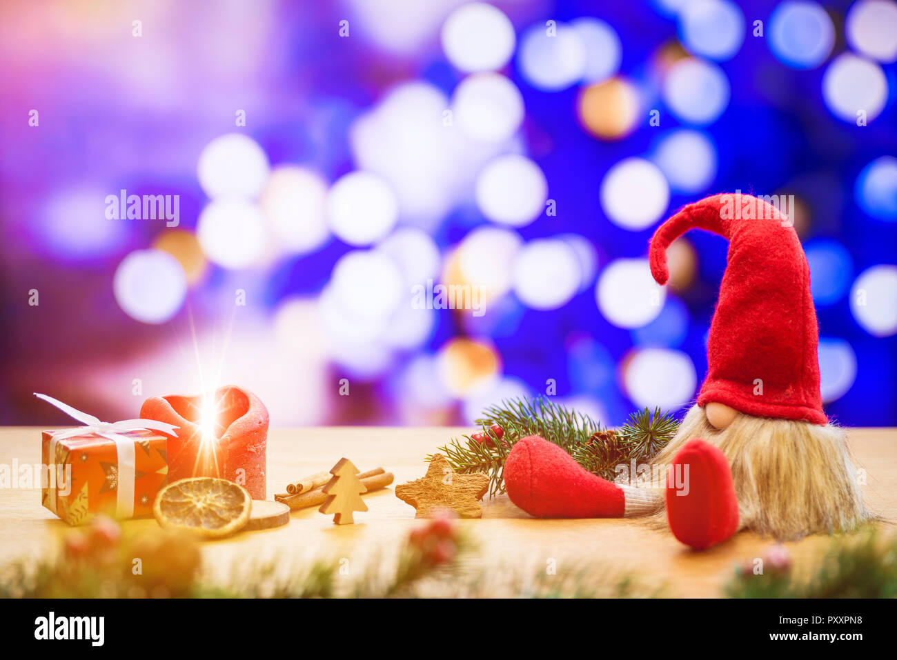 Red sitting christmas elf with bokeh lights in background surrounded by christmas decorations as gift box and ignited advent candle - Stock Image