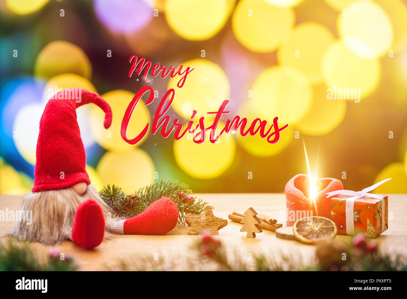 Red sitting christmas elf with merry christmas writing and bokeh lights in background surrounded by christmas decorations as gift box and ignited adve - Stock Image
