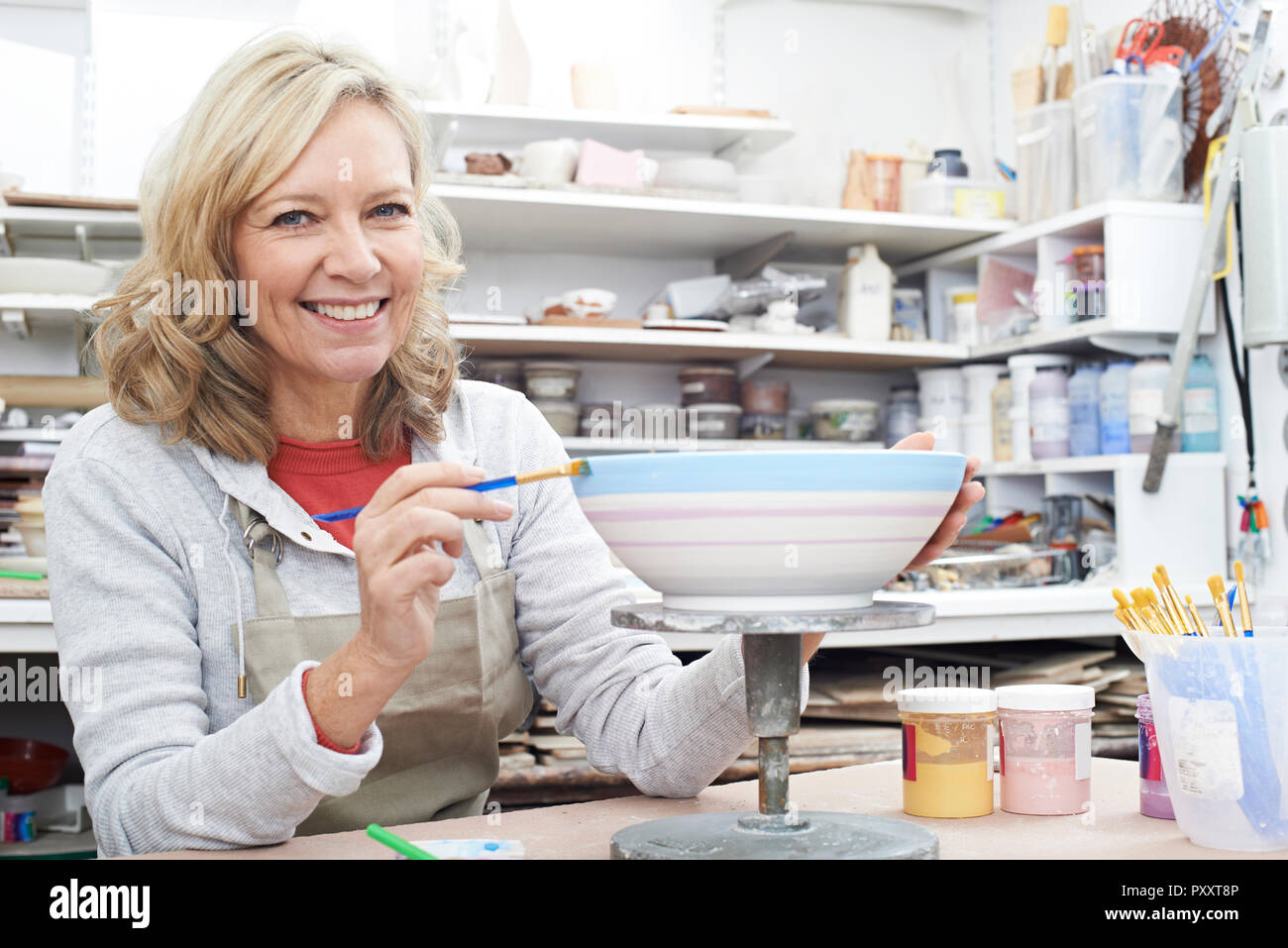 Portrait Of Mature Woman Decorating Bowl In Pottery Class - Stock Image