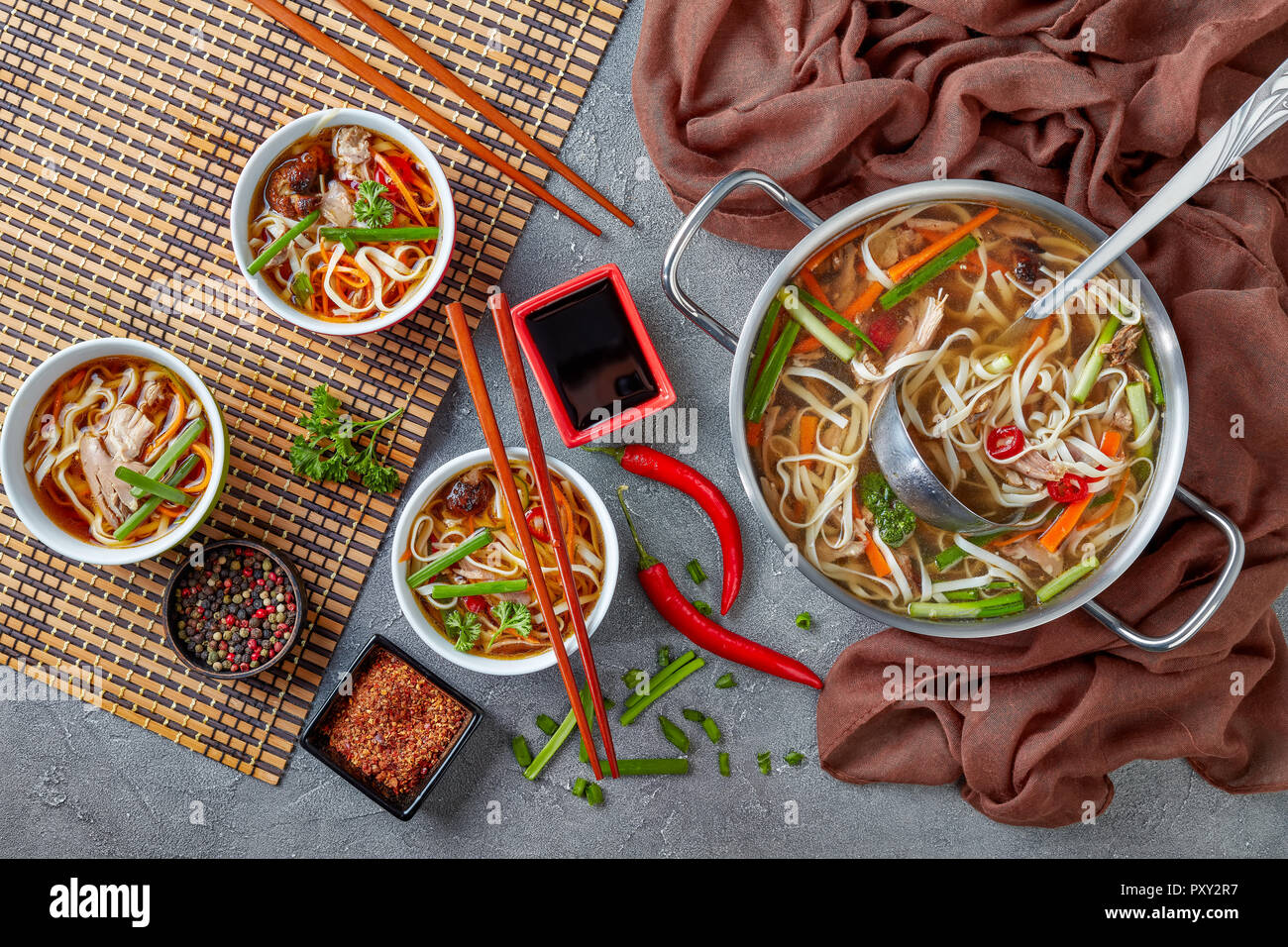 overhead view of poultry udon noodle vegetables soup in a metal casserole and served in bowls on bamboo mat with chopsticks, view from above, flatlay - Stock Image
