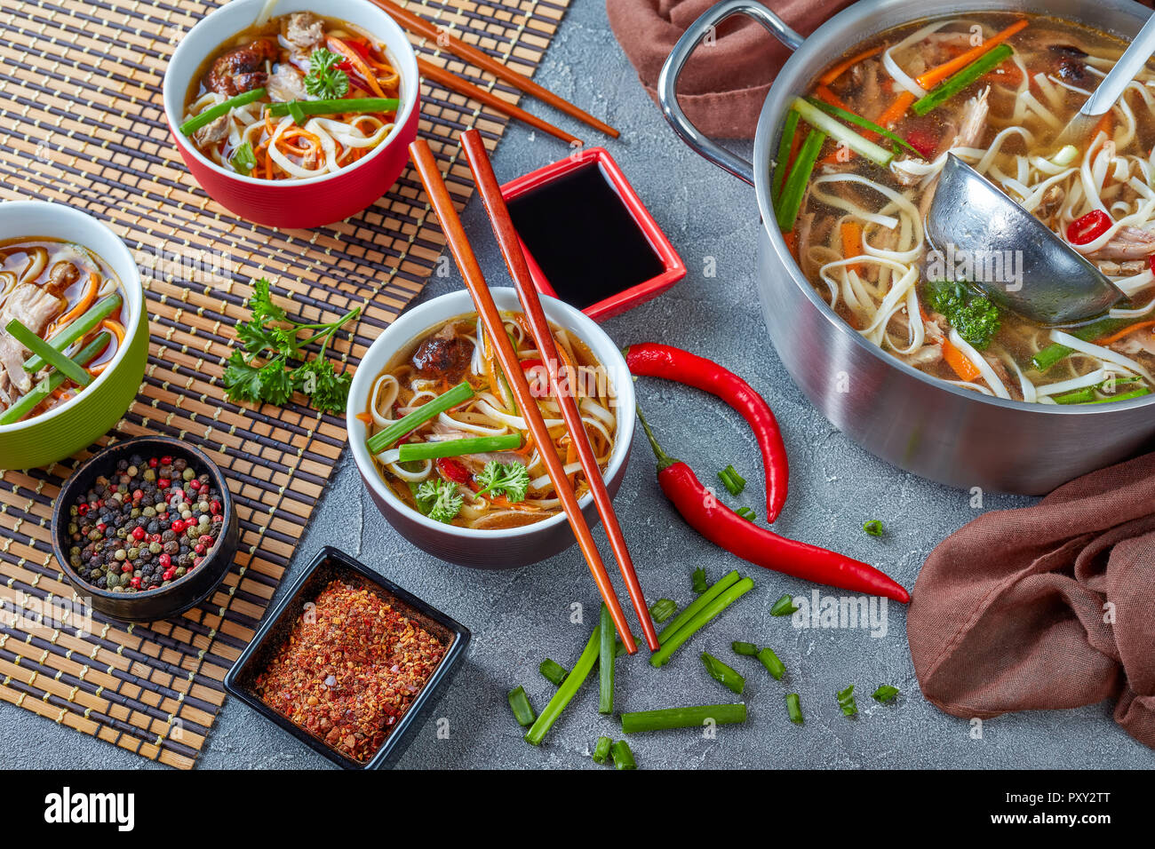 poultry udon noodle vegetables soup in a metal casserole and served in bowls on bamboo mat with chopsticks, view from above, close-up - Stock Image