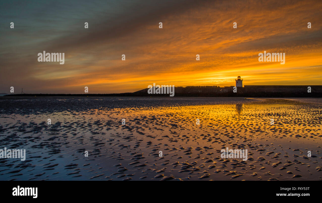 Burry Port lighthouse and beach at sunset - Stock Image
