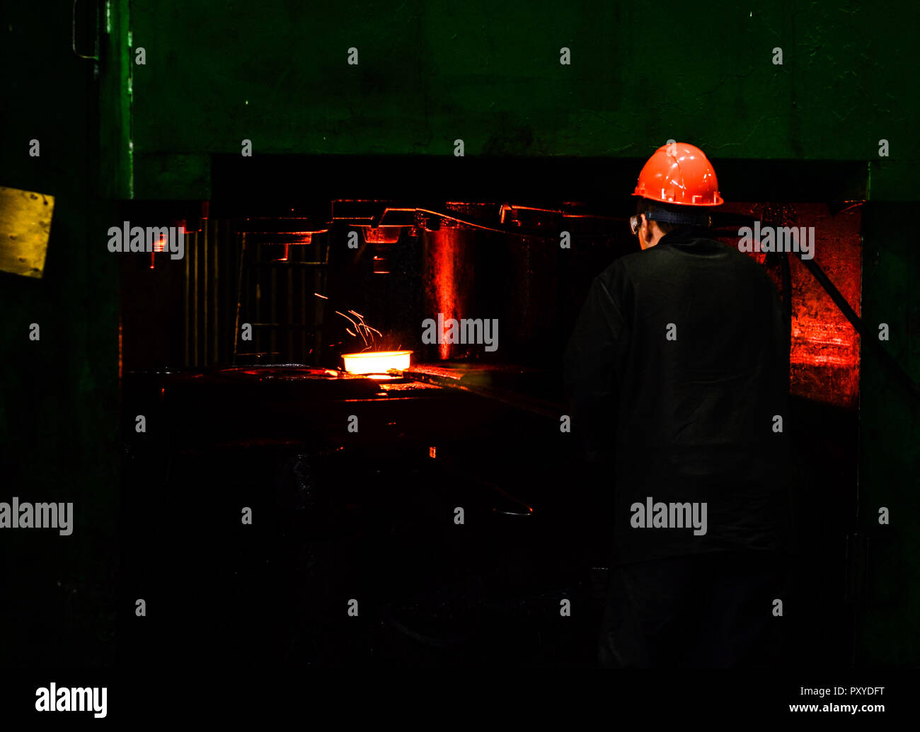 Hot iron in smeltery held by a worker. Iron melting recycling work. Heavy forging steelmaking plant and steelmaking workshop. Stock Photo