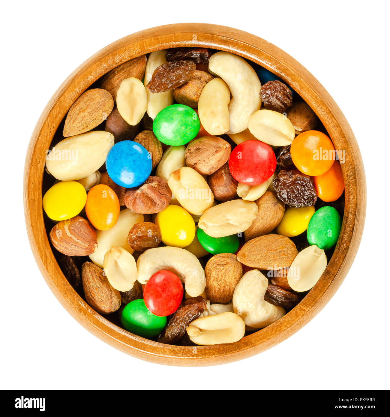 Trail mix in wooden bowl. Snack mix. Almonds, cashews, peanuts, hazelnuts, raisins and colorful chocolate candies. Food to be taken along hikes. - Stock Image