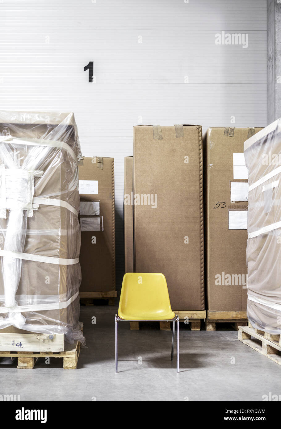 steht Kartons mit Photo Stuhl zwischen Paletten Stock TJFKc1l3