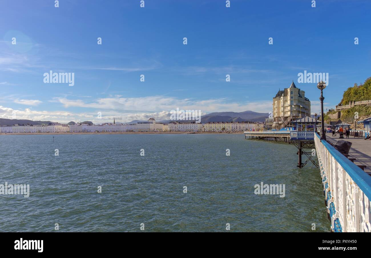 The pier at Llandudno looking towards the land. Hotels line the shore and and there hills in the distance.  A blue sky is overhead. Stock Photo