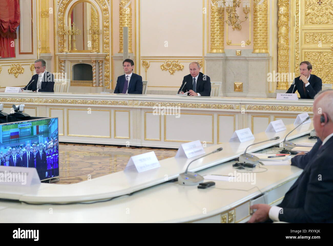 Moscow, Russia. 24th Oct, 2018. MOSCOW, RUSSIA - OCTOBER 24, 2018: Italy's Ambassador to Russia Pasquale Terracciano, Prime Minister Giuseppe Conte, Russia's President Vladimir Putin, and Industry and Trade Minister Denis Manturov (L-R back) attend a video conference to launch a REM (Russian Electric Motors) plant as part of a meeting with Italian businessmen at the Moscow Kremlin. Mikhail Klimentyev/Russian Presidential Press and Information Office/TASS Credit: ITAR-TASS News Agency/Alamy Live News - Stock Image