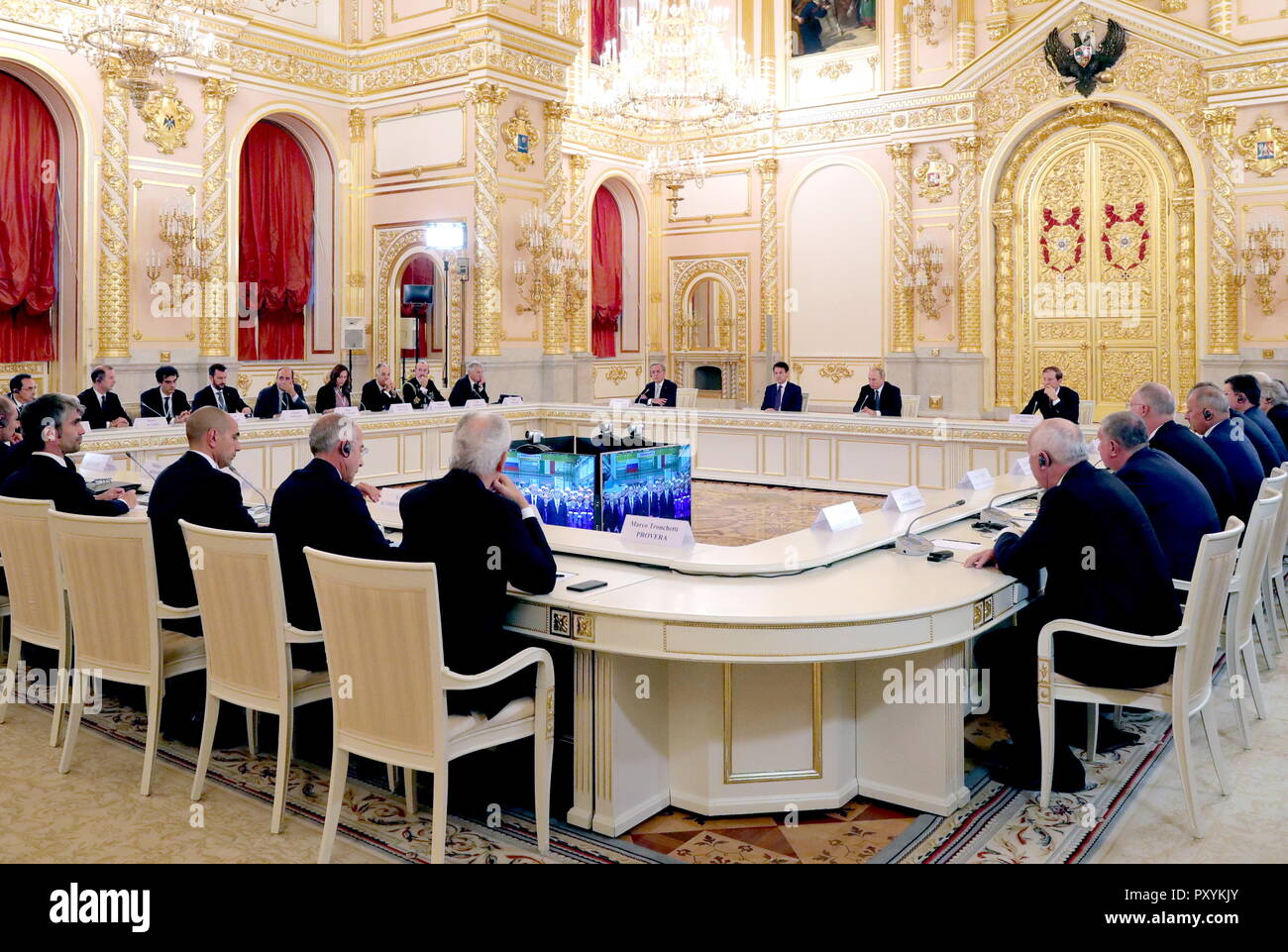 Moscow, Russia. 24th Oct, 2018. MOSCOW, RUSSIA - OCTOBER 24, 2018: Russia's Industry and Trade Minister Denis Manturov, President Vladimir Putin, Italy's Prime Minister Giuseppe Conte, and Ambassador to Russia Pasquale Terracciano (R-L back) attend a video conference to launch a REM (Russian Electric Motors) plant as part of a meeting with Italian businessmen at the Moscow Kremlin. Mikhail Klimentyev/Russian Presidential Press and Information Office/TASS Credit: ITAR-TASS News Agency/Alamy Live News - Stock Image