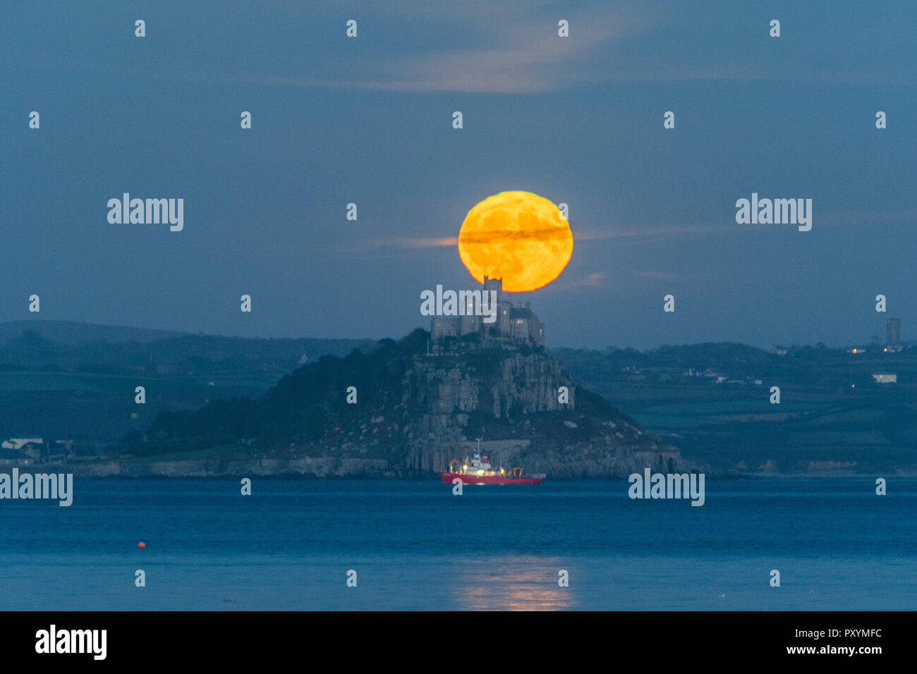 Newlyn, Cornwall, UK. 24th Oct, 2018. UK Weather. The full Hunters moon rises behind St Michaels Mount on a calm and mild autumn evening. Credit: Simon Maycock/Alamy Live News - Stock Image