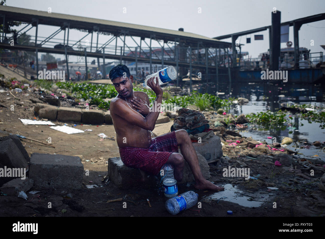 Dhaka, Dhaka, Bangladesh. 21st Mar, 2018. An uniped man seen taking a bath with some bottle of water beside Buriganga river, the water of the river becoming undesirable everyday. Credit: Ziaul Haque Oisharjh/SOPA Images/ZUMA Wire/Alamy Live News - Stock Image
