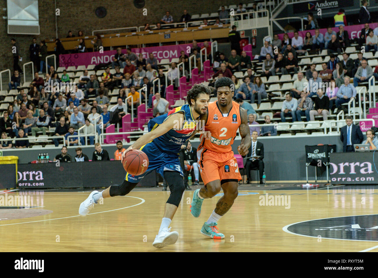 Andorra. 24th October, 2018. Mora Banc Andorra's player Michelle Vitali has the possession of the ball with the mark of Ratiopharma player Ulm Dwayne Evans. EURO CUP game between Morabanc Andorra BC and ratiopharm Ulm at Poliesportiu d´ Andorra Stadium on October 24, 2018 in Andorra La Vella. - Stock Image
