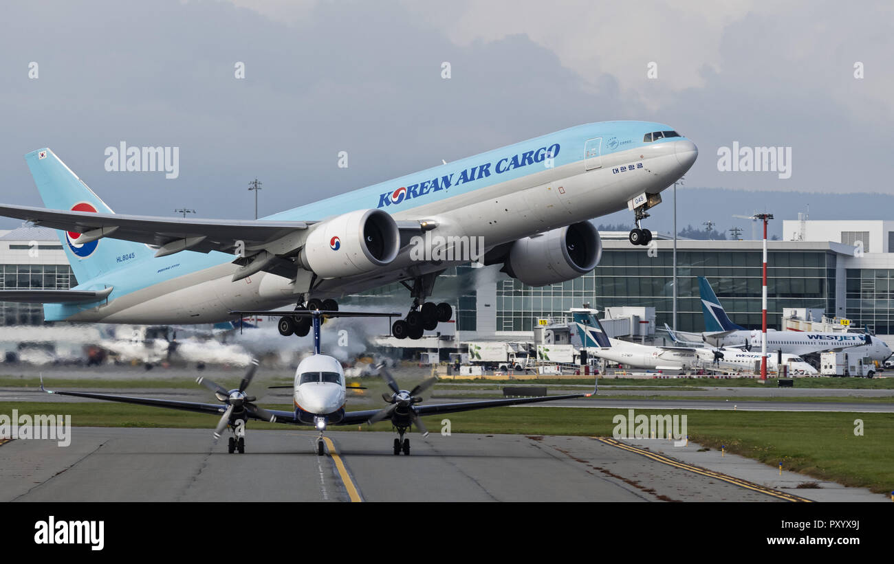 Richmond, British Columbia, Canada. 24th Oct, 2018. A Korean Air Cargo Boeing 777F (HL8045) wide-body cargo freighter takes off from Vancouver International Airport. In the foreground a Pacific Coastal Airlines Beech 1900D regional airliner taxies to the airport's South terminal. Credit: Bayne Stanley/ZUMA Wire/Alamy Live News - Stock Image