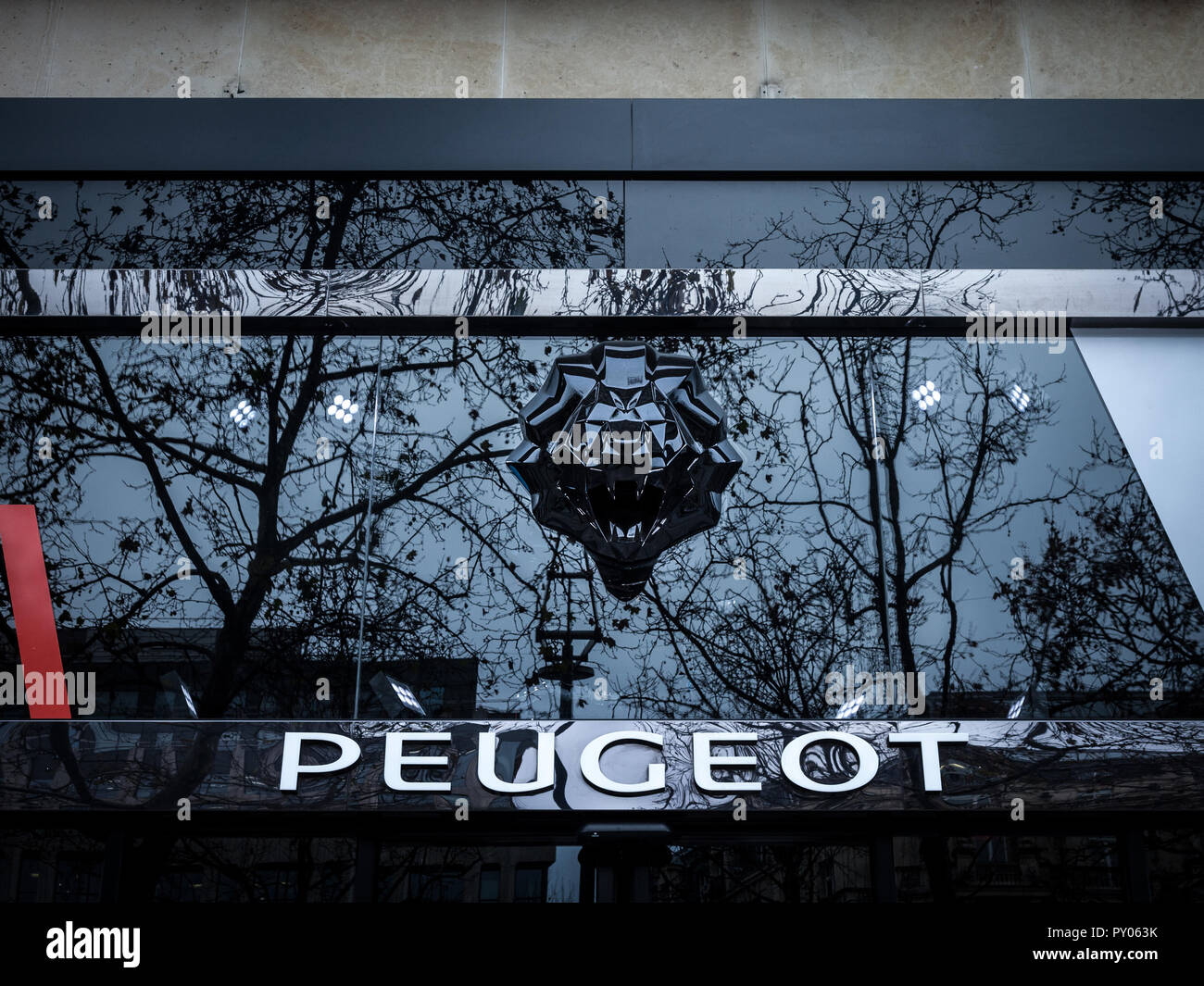 PARIS, FRANCE - DECEMBER 20, 2017: Peugeot logo on their showroom of Champs Elysees with its distinctive Lion. Peugeot, part of PSA group, is one of m - Stock Image