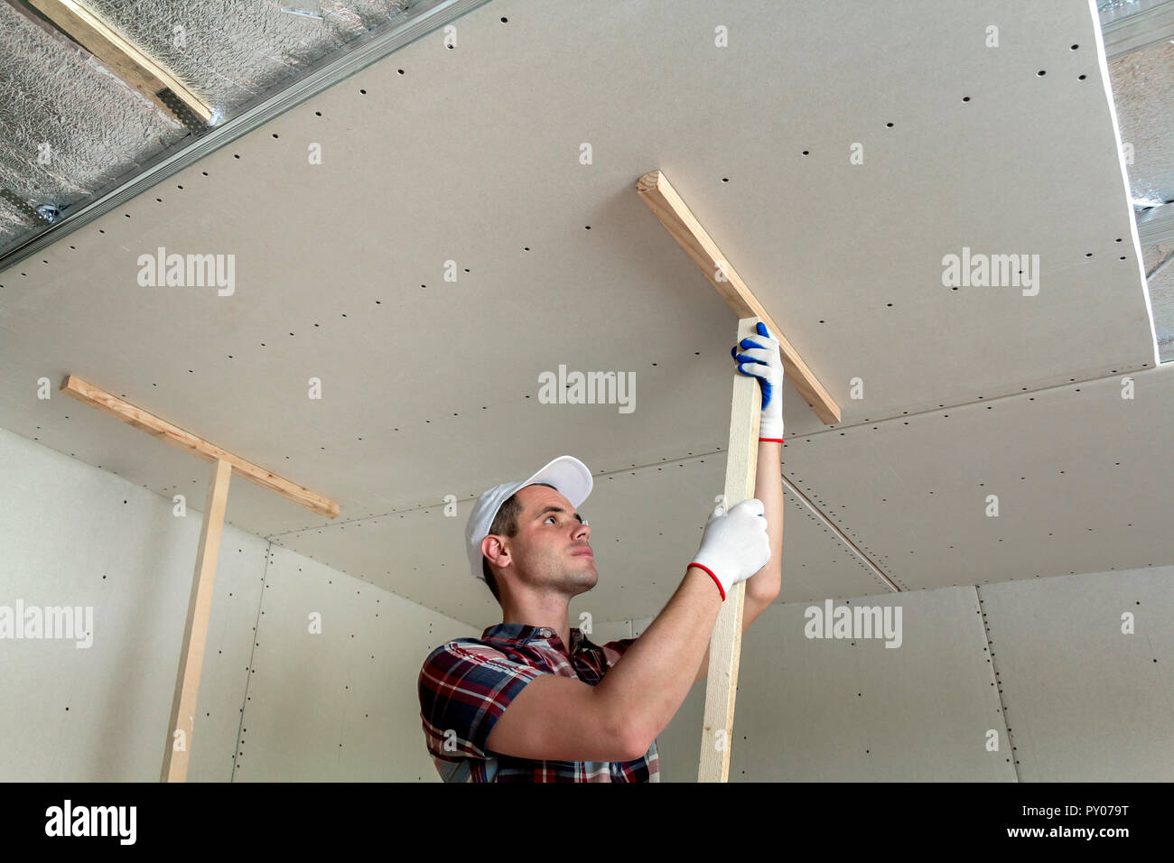 Young Worker In Protection Work Gloves Fixing Wooden Holders