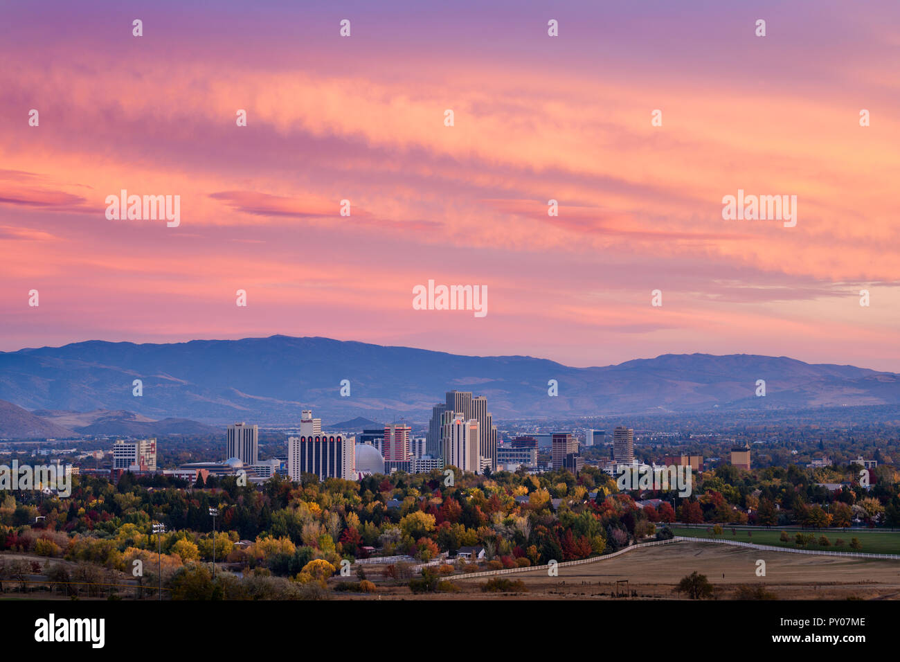 A dramatic sunset over the downtown Reno, Nevada casino skyline with fall colors from Rancho San Rafael Park in foreground. - Stock Image