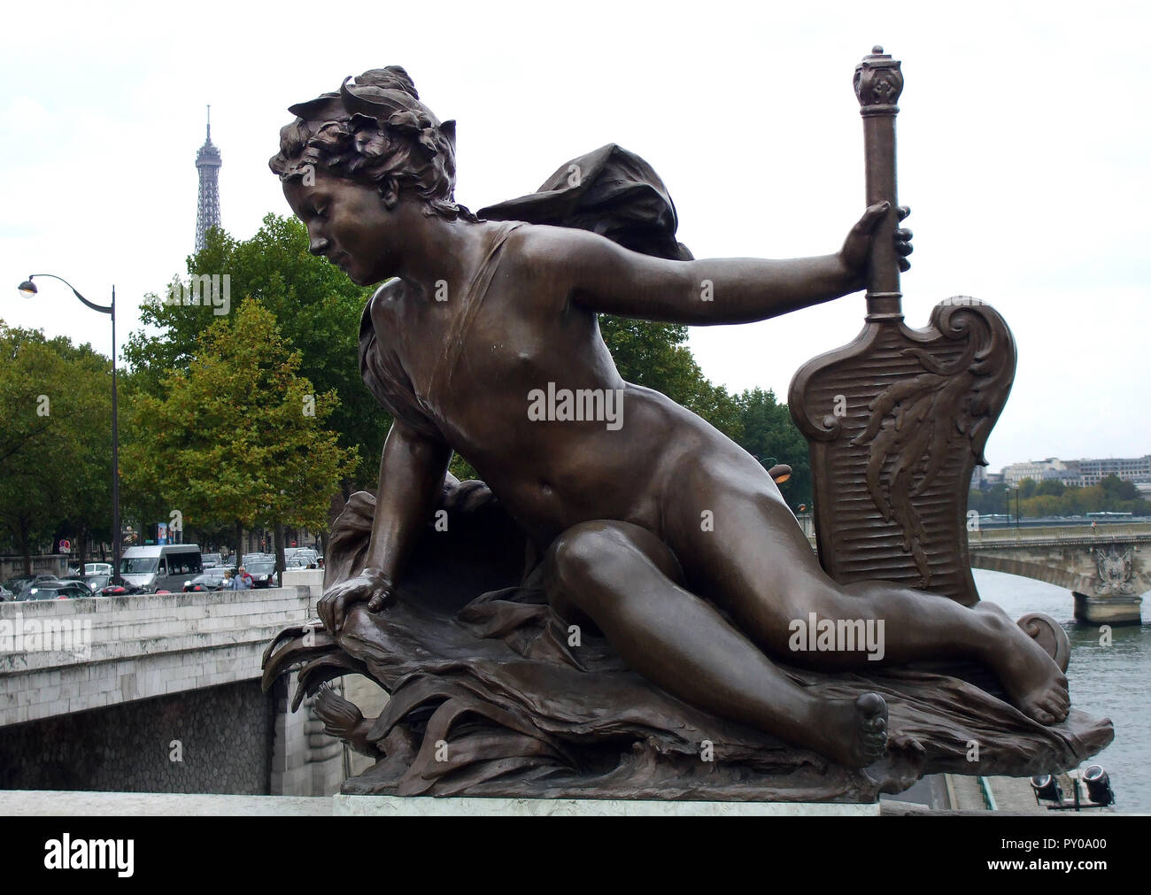 A bronze angelic statue on one of the bridges that cross the River Seine in Paris. The Eiffel tower can be seen in the background. - Stock Image