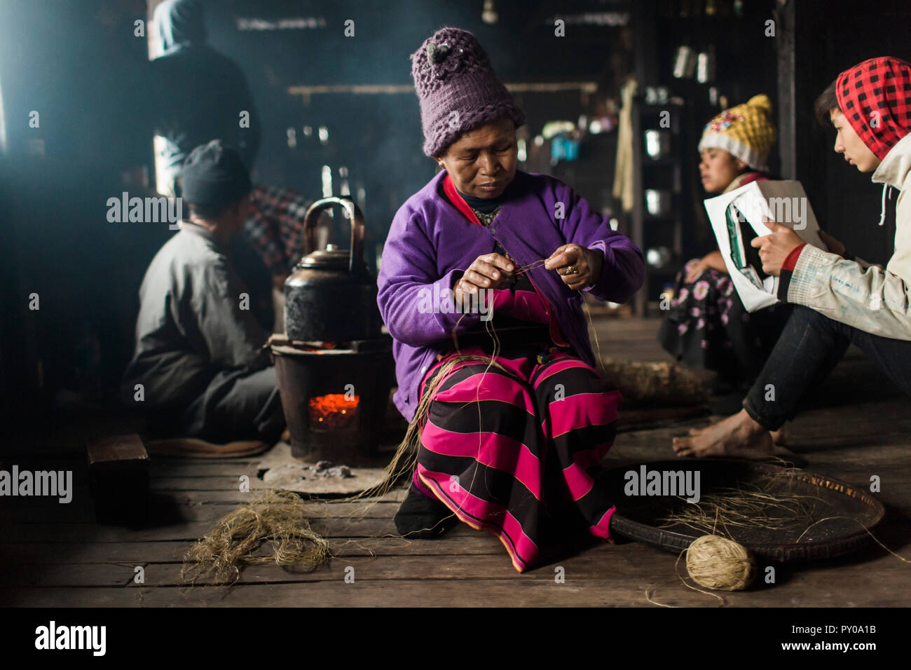 Elderly woman wearing knit hat knitting indoors in small rural house, Myanmar, Shan, Myanmar - Stock Image
