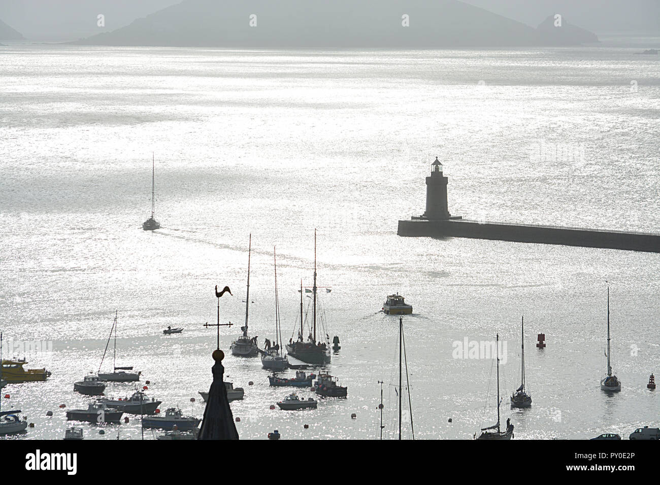 Guernsey Island, Chanel Island. View at harbour, silver ocean, lantern and ship. Stock Photo