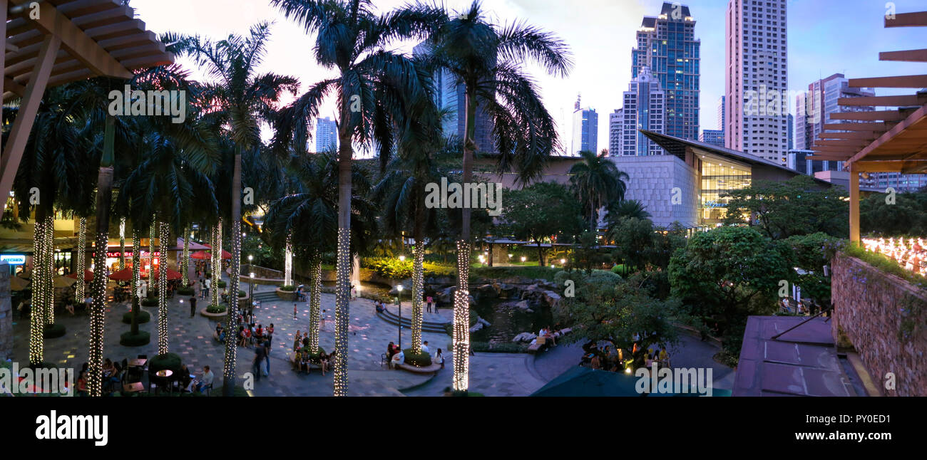 Palm trees and people in Greenbelt Park in city of Makati, Philippines - Stock Image
