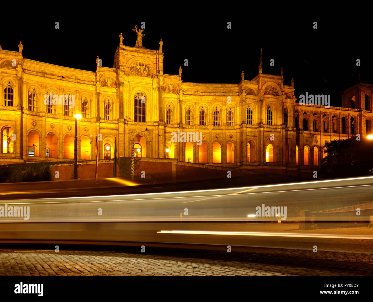 the historical building Maximillianeum in Munich, city of Bavaria, part of Germany at night with light rays from a passing street car by long exposure - Stock Image