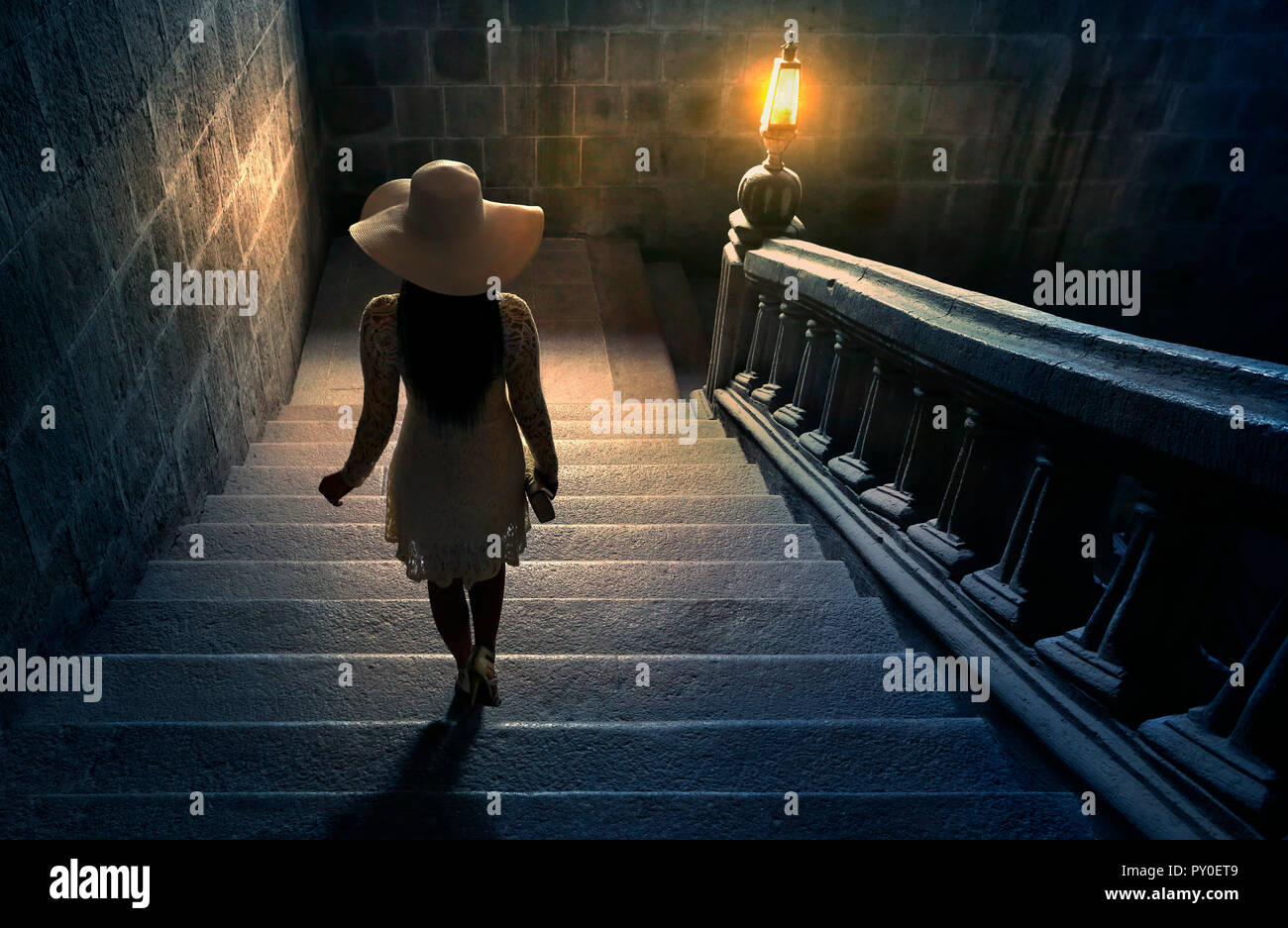 Woman in white lace dress and hat walking down stairs on colonial staircase in San Agustin Church, Manila, Philippines Stock Photo
