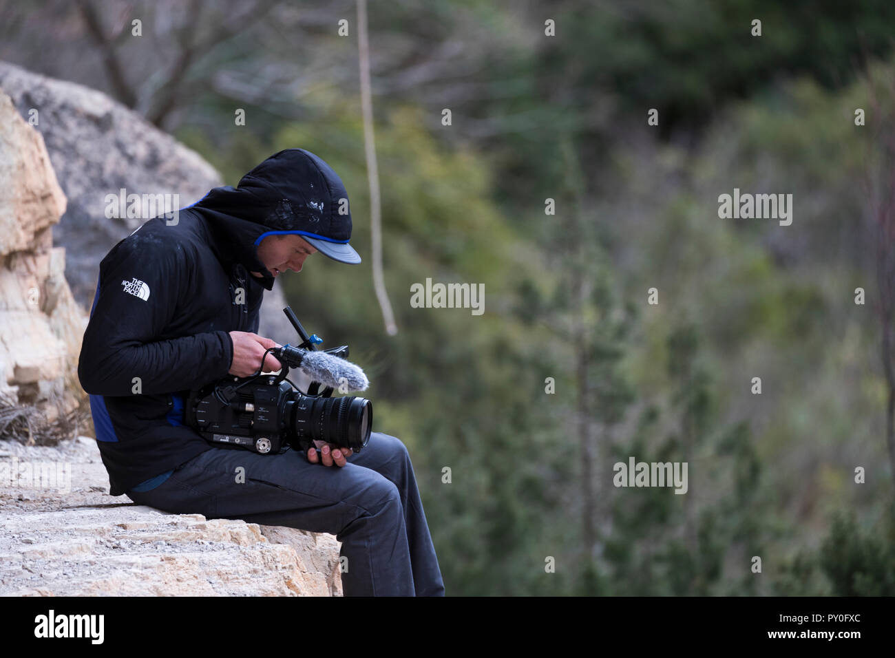 Male videographer sitting on rock formation, pointing his camera and filming something in distance,  Siurana, Catalonia, Spain - Stock Image