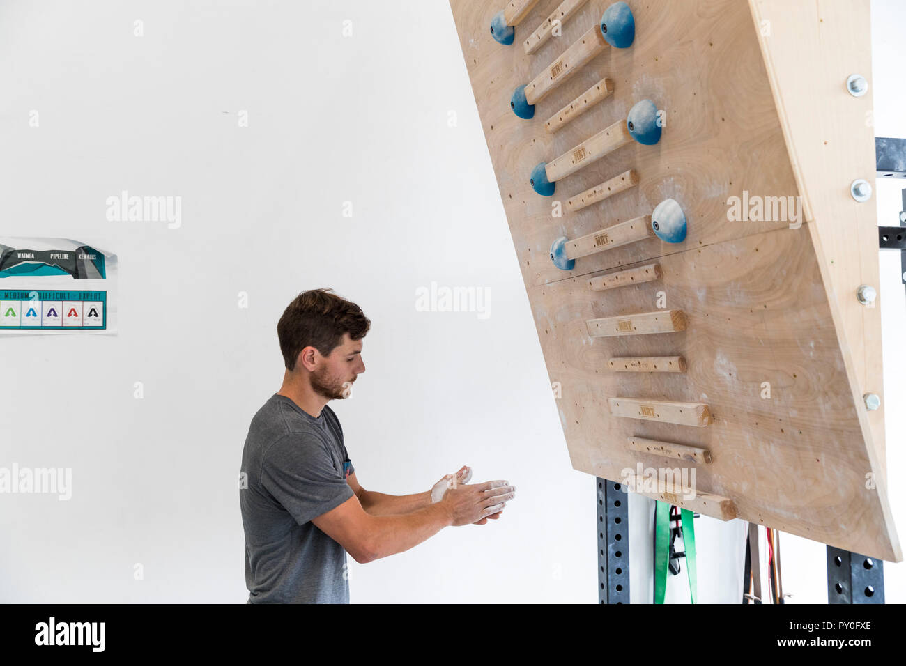 Male climber preparing to train on campus wall at indoor climbing gym, Oahu Hawaii, USA - Stock Image