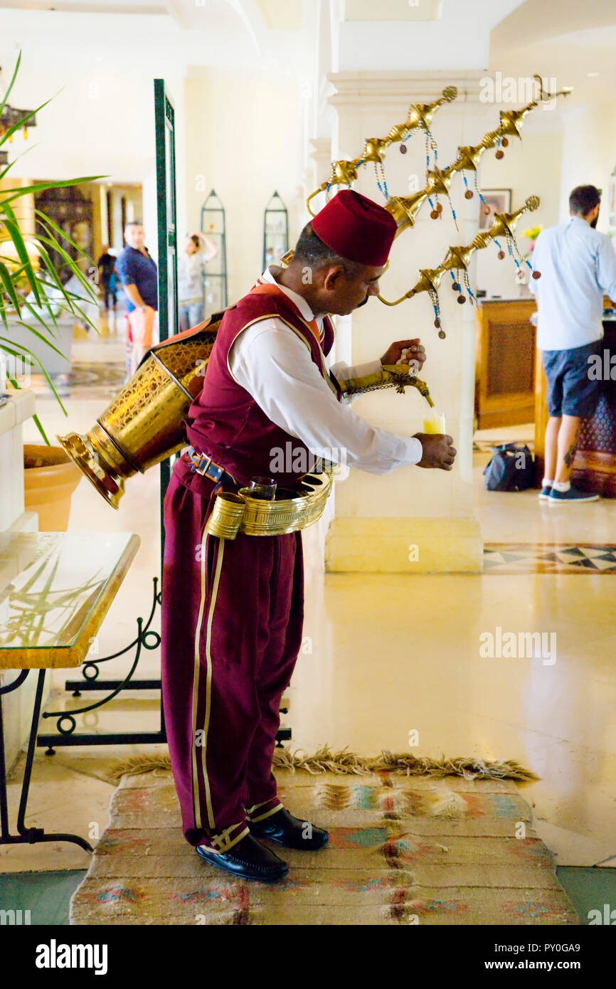 An Arabic man, dressed in traditional Ottoman style clothing, pours fruit juice from a large copper, adorned, spouted receptacle on his back, in a hotel lobby, Madaba Governorate, Jordan - Stock Image