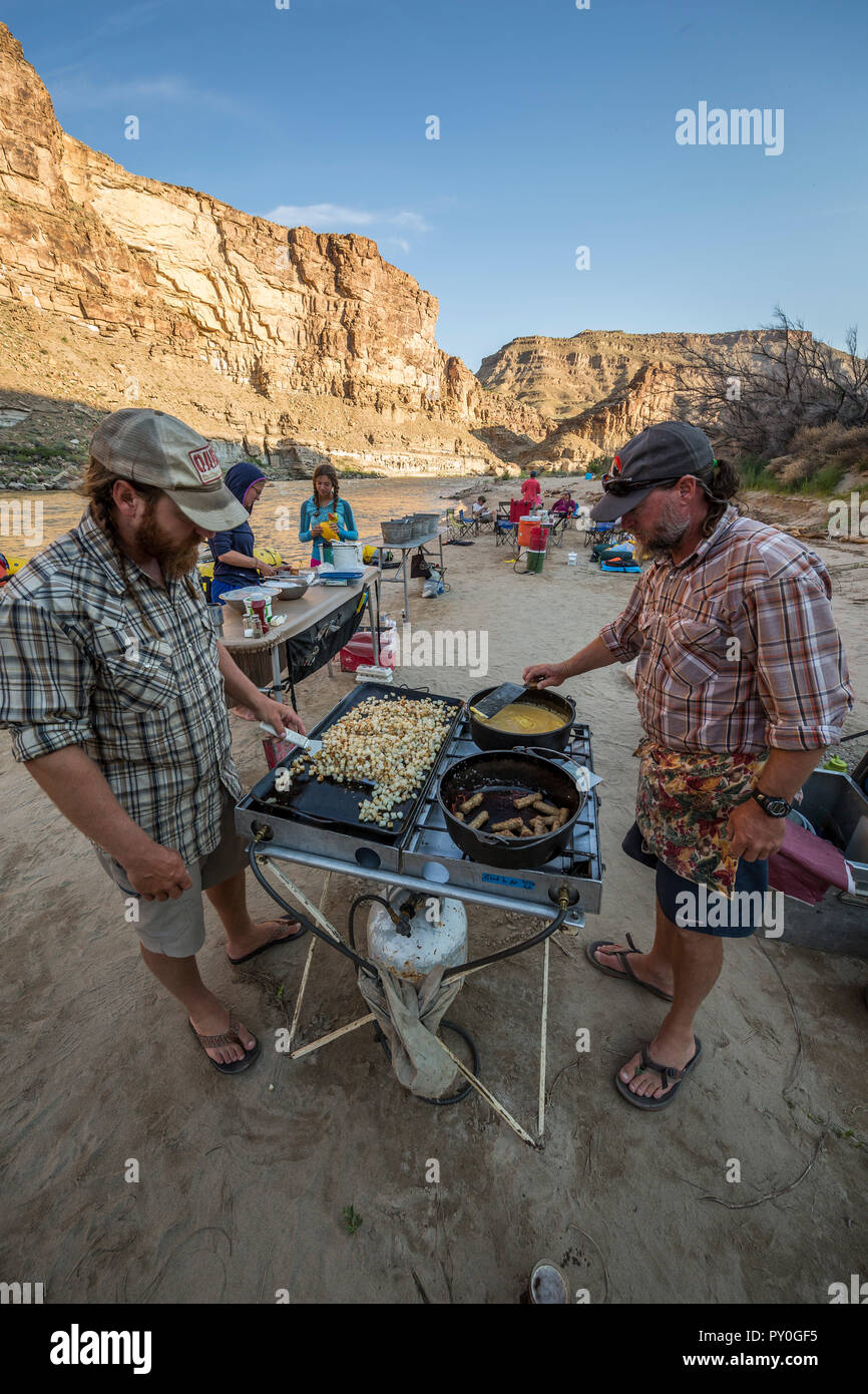 Two men cooking meal in outdoor kitchen during rafting trip, Desolation/Gray Canyon section, Utah, USA - Stock Image
