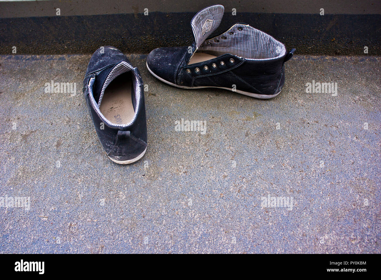 blue sneakers shoes without laces abandoned in the street - Stock Image