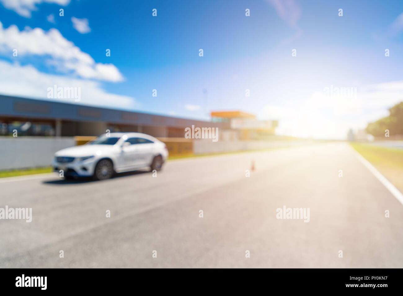 Abstract blur and bokeh. White Luxury car in racetrack and speed racing back ground clear sky. Sunlight and flare concept. - Stock Image