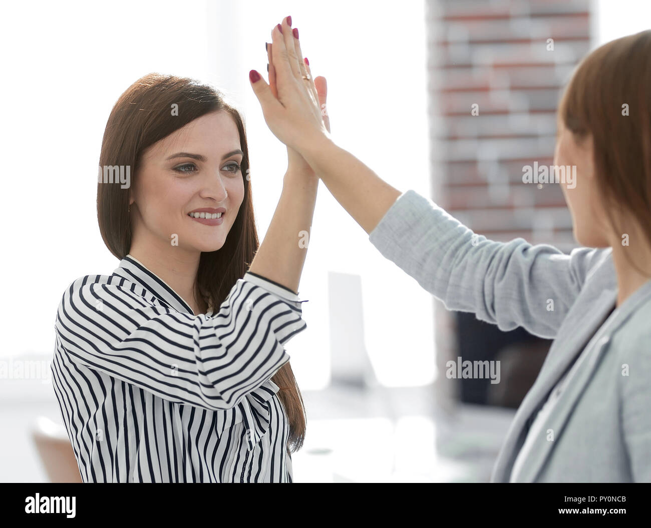 two young co-workers giving each other a high five - Stock Image
