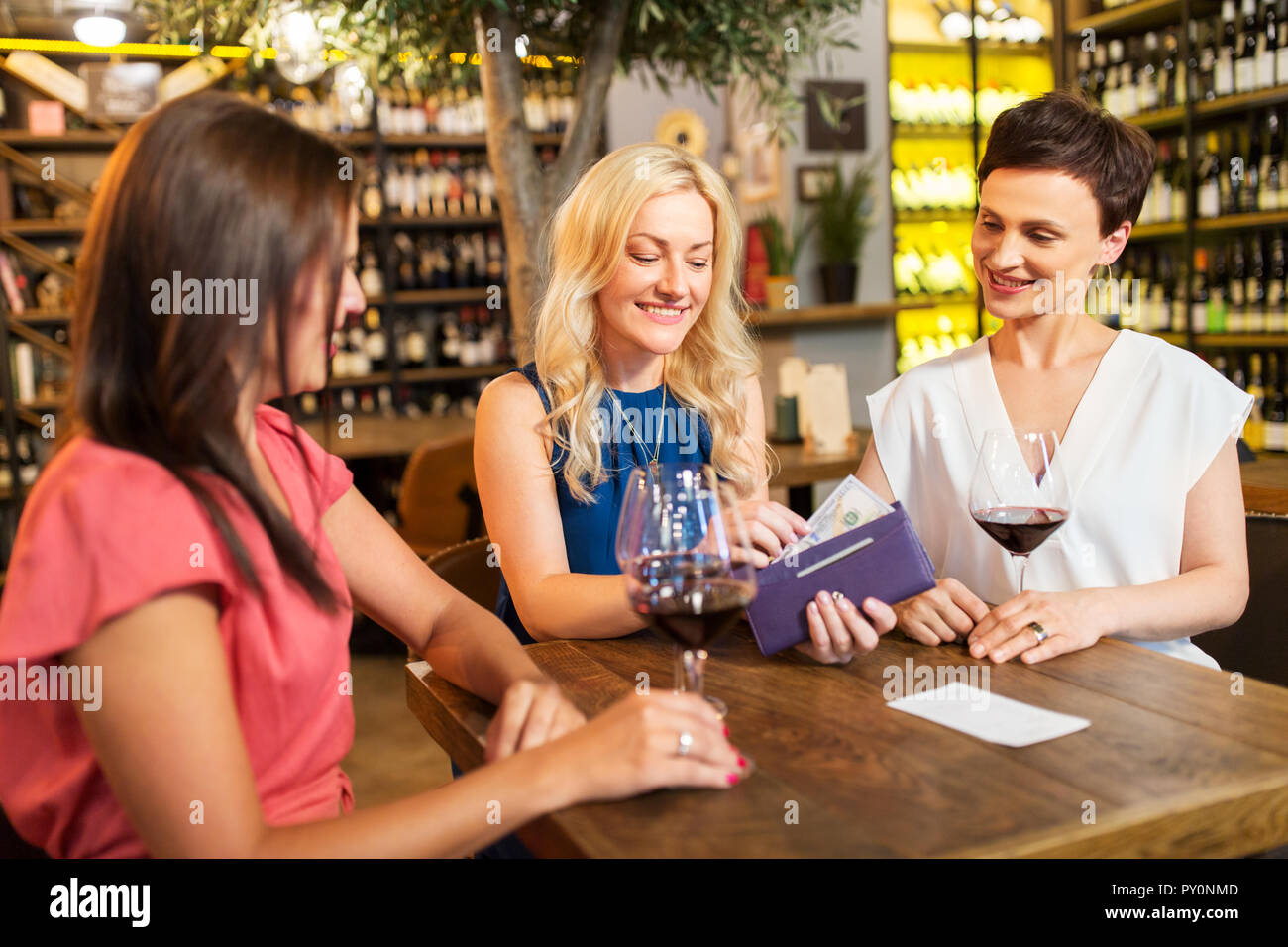 Women Paying Bill At Wine Bar Or Restaurant Stock Photo