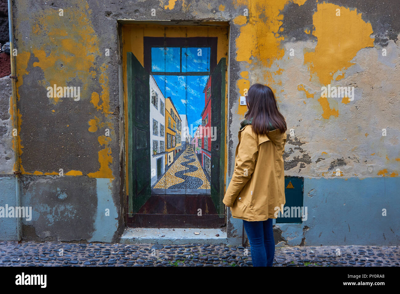 Girl Woman Traveler looking at a painted door on a traditional street in Funchal, Madeira - Stock Image