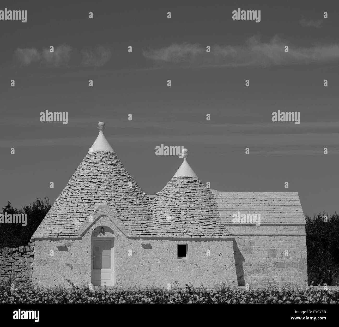 Traditional white-washed trulli house with conical roof, located outside Locorotondo in the Itria Valley, Puglia, Southern Italy, in monochrome. - Stock Image