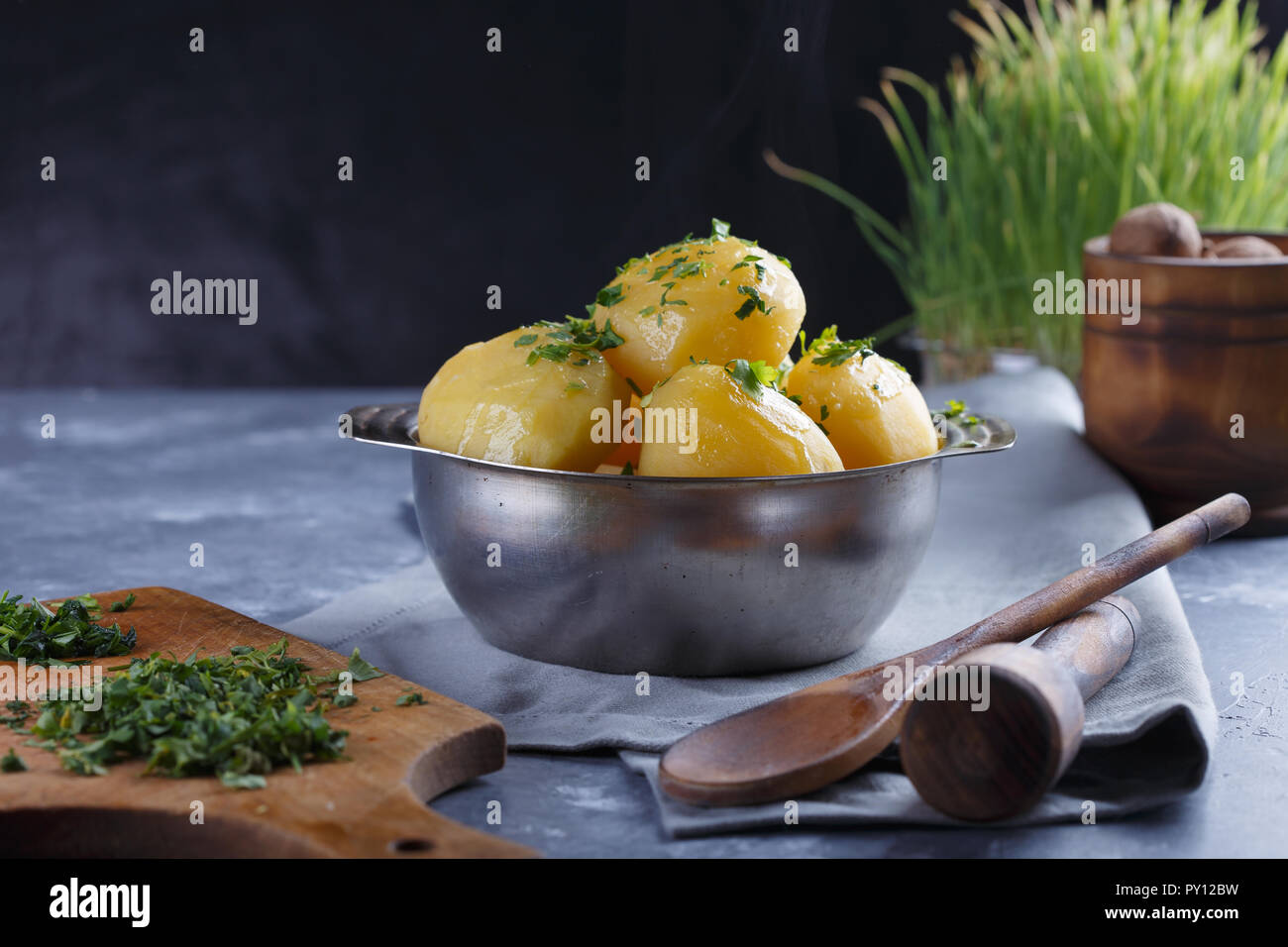 Hot boiled potatoes in a plate dusted with greens and smoke on a gray background. Stock Photo