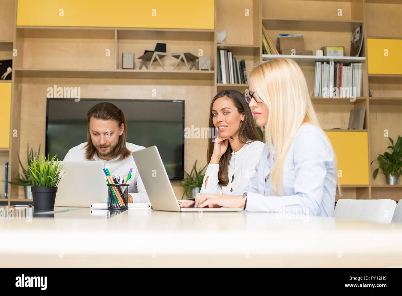 Cheerfull business team working together to achieve better results - Stock Image