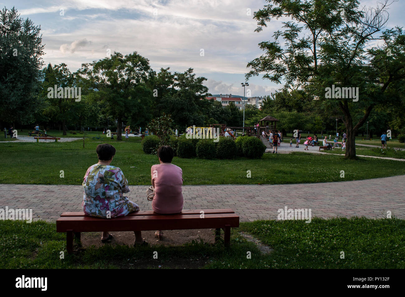 Mostar: Bosnian women talking on a bench and watching the children playing in the Zrinjski City Park, a public park on the western side of the city - Stock Image