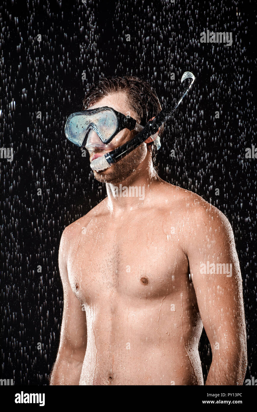 portrait of shirtless man in swimming mask with snorkel standing under water drops isolated on black - Stock Image