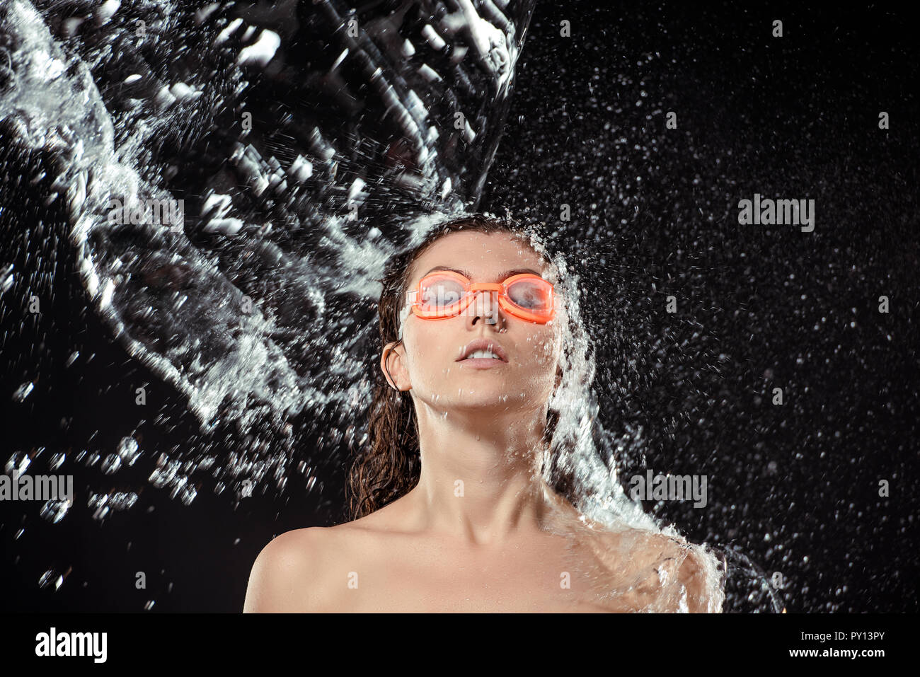 portrait of woman in swimming goggles swilled with water isolated on black - Stock Image