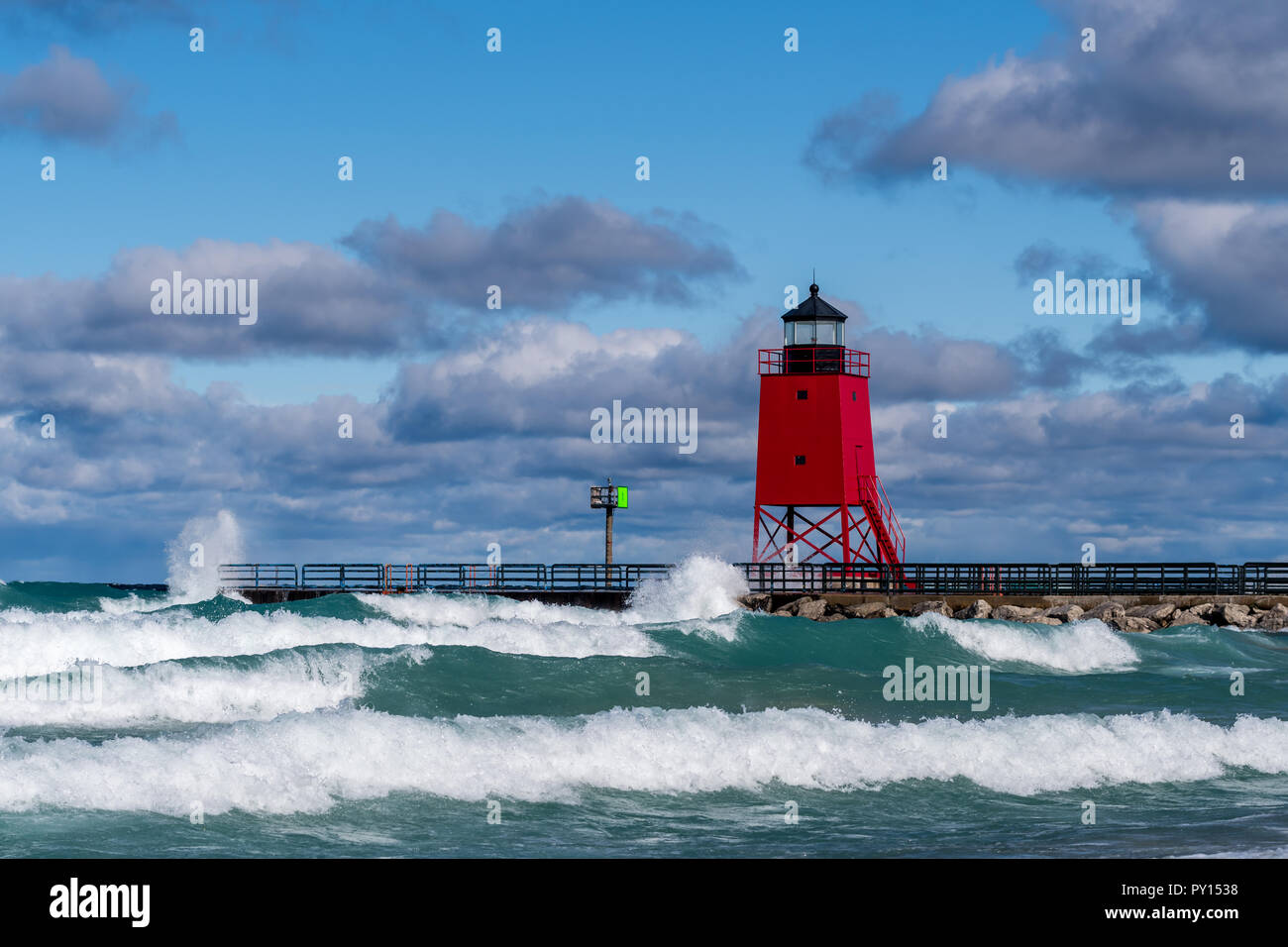 Large waves breaking in front of the Charlevoix South Pier lighthouse in Charlevoix, Michigan, USA. - Stock Image