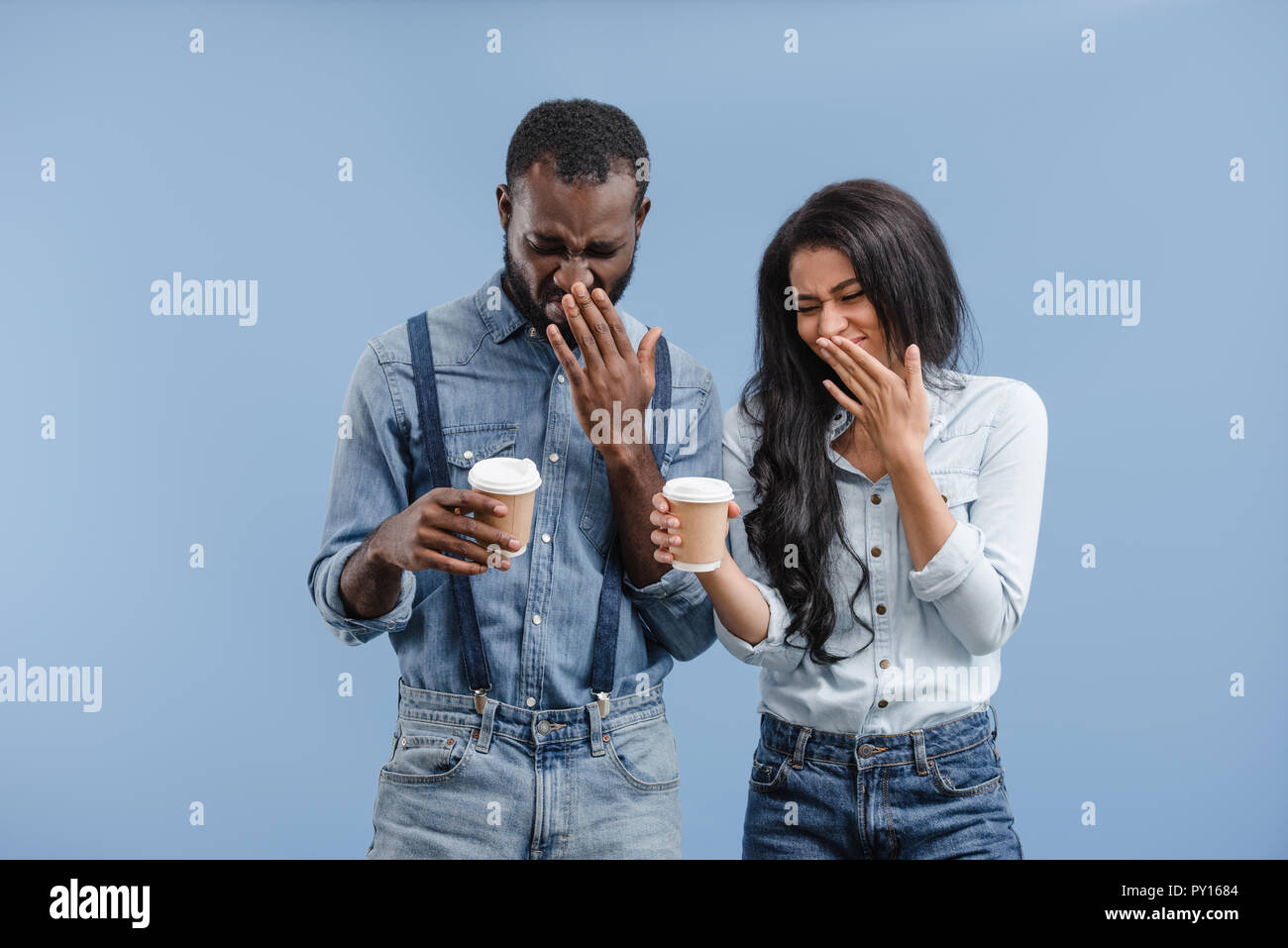 grimacing african american couple holding coffee to go and covering noses isolated on blue - Stock Image