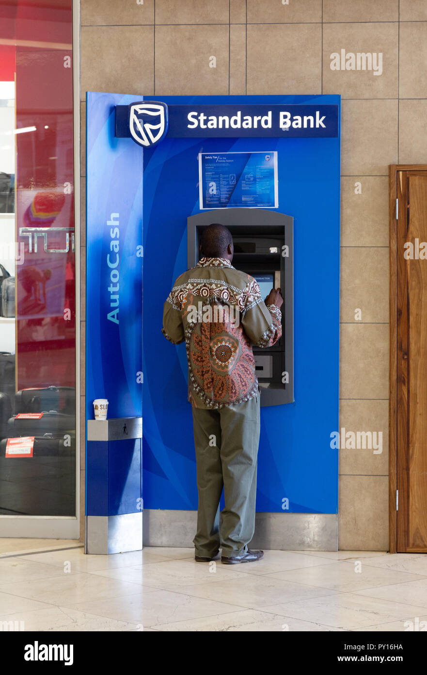 Namibia bank ATM - a namibian man using a Standard Bank cash machine, Windhoek, Namibia Africa - Stock Image